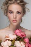Primer del retrato de una mujer rubia hermosa joven con las flores frescas Fotos de archivo