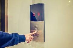 Primer del ` s de la mujer que empuja un botón manualmente del elevador Imagen de archivo