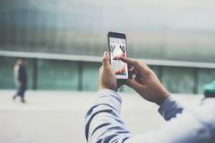 Primer del smartphone con los gráficos, los diagramas y las cartas en la pantalla en las manos masculinas Imagen de archivo libre de regalías