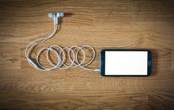 Primer del smartphone negro con la pantalla blanca con los auriculares encendido Fotos de archivo libres de regalías