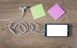 Primer del smartphone negro con la pantalla blanca con los auriculares, s Imagenes de archivo