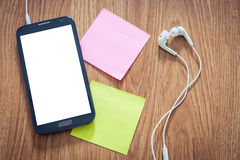 Primer del smartphone negro con la pantalla blanca con los auriculares, s Foto de archivo libre de regalías