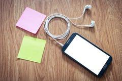 Primer del smartphone negro con la pantalla blanca con los auriculares, s Imagen de archivo libre de regalías