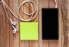 Primer del smartphone negro con los auriculares y las notas pegajosas encendido Fotos de archivo libres de regalías