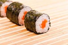 Primer del sushi en fila en la estera de bambú Foto de archivo libre de regalías