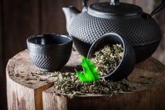 Primer del té verde fresco con la tetera y la taza del hierro Imagen de archivo libre de regalías