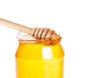 Primer del tarro abierto de la miel en el fondo blanco con el cazo de madera de la miel dentro Fotografía de archivo libre de regalías