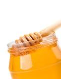 Primer del tarro abierto de la miel en el fondo blanco con el cazo de madera de la miel dentro Fotografía de archivo