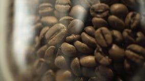 Primer del tarro de cristal por completo de granos de café marrones frescos que se colocan en el estante o la tabla en el caffe o metrajes