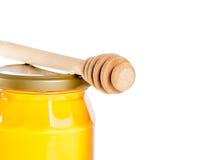Primer del tarro de la miel en el fondo blanco con el cazo de madera de la miel Imágenes de archivo libres de regalías