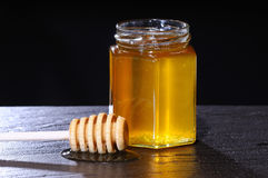Primer del tarro de la miel y del palillo de madera Imagen de archivo libre de regalías