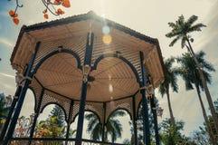Primer del techo colorido del gazebo en el medio del jardín por completo de árboles, en día soleado en São Manuel Imagen de archivo