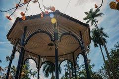 Primer del techo colorido del gazebo en el medio del jardín por completo de árboles, en un día soleado brillante en São Manuel Imagen de archivo