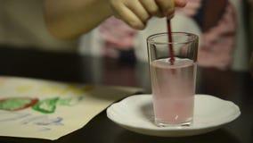 Primer del tiro de la mano de un niño que limpia un cepillo manchado pintura en un vaso de agua almacen de metraje de vídeo