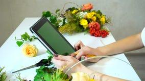 Primer del tiroteo de manos del florista de sexo femenino con la tableta que busca para la información sobre las flores y escribe metrajes