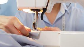 Primer del trabajo de acabado de la modista de la mano de una mujer con una máquina de coser en el lugar de trabajo almacen de video