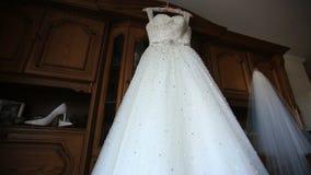 Primer del vestido de boda de marfil lujoso que cuelga para arriba por la ventana en el fondo de madera del estante almacen de metraje de vídeo