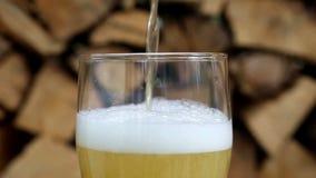 Primer del vidrio de cerveza delante de la leña en la placa giratoria metrajes