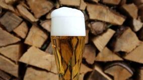 Primer del vidrio de cerveza delante de la leña en la placa giratoria almacen de metraje de vídeo