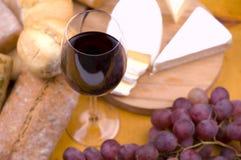 Primer del vidrio de vino con el alimento en fondo Imagen de archivo libre de regalías