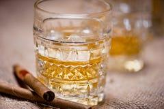 Primer del vidrio del whisky en las rocas con los cigarros y el fondo del vintage Imagen de archivo