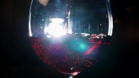 Primer del vidrio que vierte con el vino espumoso rojo en la oscuridad con la luz blanca en el fondo Cantidad com?n Vista a almacen de video