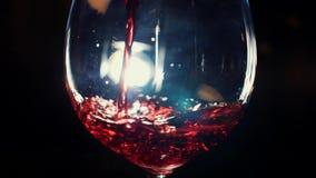 Primer del vidrio que vierte con el vino espumoso rojo en la oscuridad con la luz blanca en el fondo Cantidad com?n Vista a metrajes