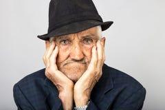 Primer del viejo hombre expresivo que sostiene la cara en manos Foto de archivo libre de regalías