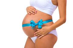 Primer del vientre embarazada con la cinta azul y el arco Concepto de embarazo Bebé recién nacido Fotos de archivo