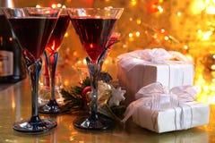 Primer del vino rojo en vidrios, vela y regalos Foto de archivo libre de regalías