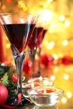 Primer del vino rojo en vidrios y luces de la vela. Foto de archivo