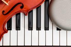 Primer del violín y del altavoz encendido al fondo del teclado de piano imagen de archivo libre de regalías