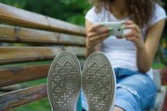 Primer del zapato de los lenguados Muchacha en vaqueros usando un teléfono móvil Fotos de archivo libres de regalías
