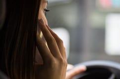 Primer dentro del vehículo de la mano del ` s de la mujer que sostiene el teléfono móvil para arriba contra el oído como en habla Fotografía de archivo libre de regalías