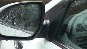 Primer, detalle de un coche bajo la lluvia en un estacionamiento afuera 4k, c?mara lenta almacen de metraje de vídeo
