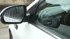 Primer, detalle de un coche bajo la lluvia en un estacionamiento afuera 4k, c?mara lenta metrajes