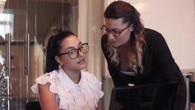 Primer Dos mujeres de negocios jovenes discuten un proyecto del negocio en una oficina usando un ordenador almacen de video
