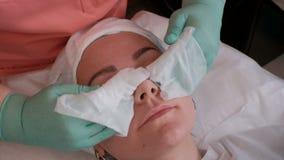 Primer El cosmetólogo frota la cara de una muchacha hermosa con los trapos mojados Las manos de las mujeres en guantes verdes El  almacen de video