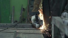 Primer - el herrero In Protective Gloves examina barras de hierro metrajes