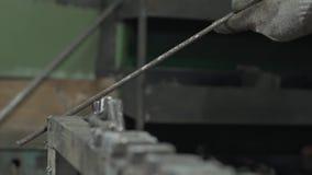 Primer - el herrero In Protective Gloves examina barras de hierro almacen de metraje de vídeo