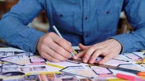 Primer: el hombre dobla sobre el escritorio y hace notas con una pluma, inclinándose en la tabla Primer: una pluma de la escritur almacen de video