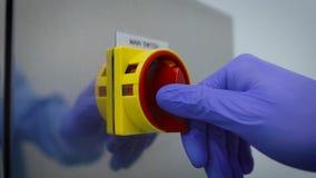Primer El trabajador en guantes incluye el interruptor principal del equipo, instalación Un interruptor rojo grande que proporcio metrajes
