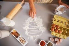 Primer en árbol del dibujo del ama de casa en la tabla de cocina con la harina Imagenes de archivo