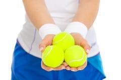 Primer en 3 pelotas de tenis a disposición de jugador de tenis Imagenes de archivo