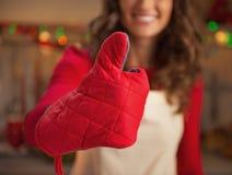 Primer en ama de casa joven en los guantes de la cocina que muestran los pulgares para arriba Foto de archivo libre de regalías
