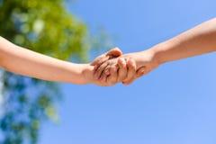 Primer en apretón de manos entre los niños en fondo del cielo azul Foto de archivo