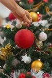 Primer en bola colgante de la Navidad de la mano de la mujer Foto de archivo