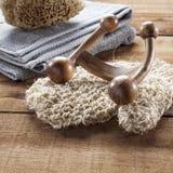 Primer en el accesorio del masaje y esponja natural en el fondo de madera para la relajación Foto de archivo