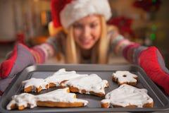 Primer en el adolescente sonriente que saca la cacerola de galletas frescas Imágenes de archivo libres de regalías