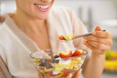 Primer en el ama de casa joven que come la ensalada de fruta fresca Imagen de archivo